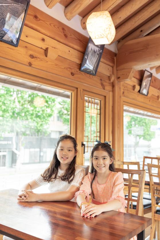(왼쪽)허시은·이수안 학생모델이 장안사랑채에 있는 카페 2층에서 통유리창 곁에 앉았다. 수원한옥기술관,장안사랑채는 밖을 내다볼 수 있고 밖에서도 안을 볼 수 있는 통유리창을 적극 활용했다. 신한옥의 특징으로 소통성, 개방성을 드러내기 위해서다.
