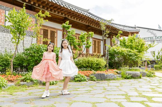 이수안(왼쪽)·허시은 학생모델이 경기도 수원 장안사랑채 뒤뜰에서 저마다 옷자락을 들고 웃어 보였다.