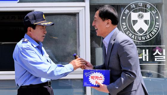 김선재 배대재 총장(오른쪽)이 17일 박봉을 쪼개 발전기금을 기탁한 경비원 조동주씨에게 음료를 전달하고 있다. [사진 배재대]