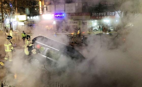 4일 오후 8시 40분쯤 경기도 고양시 일산동구 지하철 3호선 백석역 인근 지하 도로에 매설된 지역 열수송관이 터지는 사고가 발생했다. 이날 소방대원들이 함몰된 도로로 추락한 승용차를 견인하고 있다. 김성룡 기자