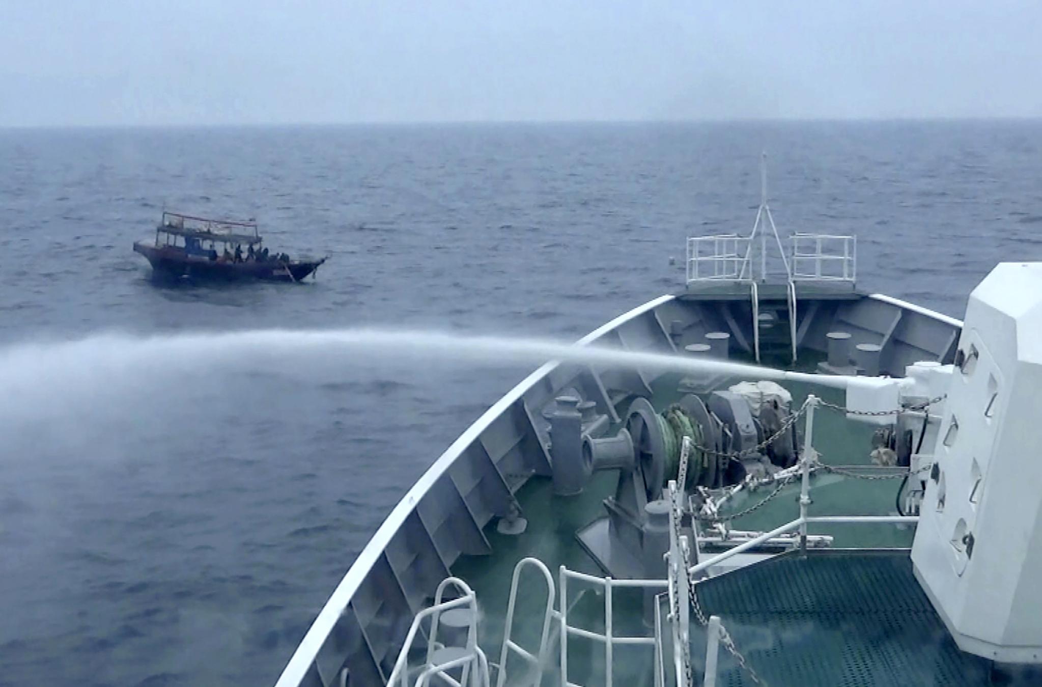 일본 해상 보안청은 18일 배타적 경제수역(EEZ)을 침범해 불법 조업하는 북한어선을 쫒아내는 사진을 공개했다. 지난 5월 일본 해안 경비대 배가 물대포를 쏴 북한 어선을 쫒아내고 있다. [AP=연합뉴스]