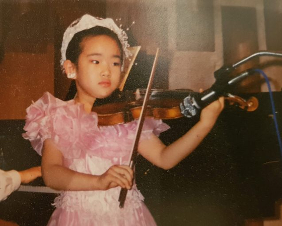 네 살 때부터 바이올린을 켰다. 어린 시절 연주하는 모습. [김신해 제공]
