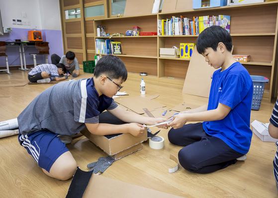 김민기(왼쪽)·이찬우 영메이커가 황소 천사 가방에 붙일 찍찍이 테이프를 재단 중이다.