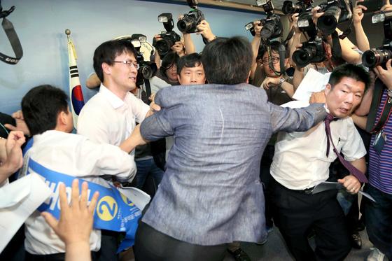 기동민 더불어민주당 의원이 2014년 7월 8일 7·30 재보선 서울 동작을 후보로 전략공천돼 국회 정론관에서 수락 기자회견을 열자 이에 반발한 허동준 전 동작을 지역위원장(왼쪽 끝)과 지지자들이 난입해 당 관계자들과 육탄전을 벌이고 있다.