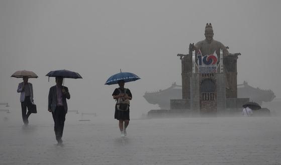 소나기가 내린 18일 서울시 종로구 광화문광장에서 시민들이 우산을 쓰고 출근을 하고 있다. [연합뉴스]