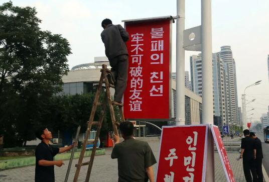 북한 주민들이 중국 시진핑 국가주석의 도착 직전 '불패의 친선' 표어를 설치하고 있다. [사진 연합뉴스]