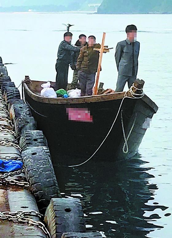 지난 15일 북한 선원 4명이 탄 어선이 연안에서 조업 중인 어민의 신고로 발견됐다는 정부 당국의 발표와 달리 삼척항 부두에 정박했다고 KBS가 18일 보도했다. 사진은 당시 삼척항 부두에 정박한 북한어선과 어민. [뉴스1]