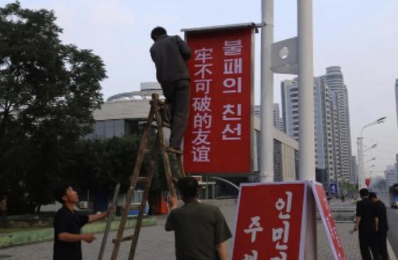 시진핑 중국 국가주석의 방북을 앞둔 19일 평양 시민들이 거리에 '불패의 친선'이라 적힌 플래카드를 걸고 있다. [중국 신화사]