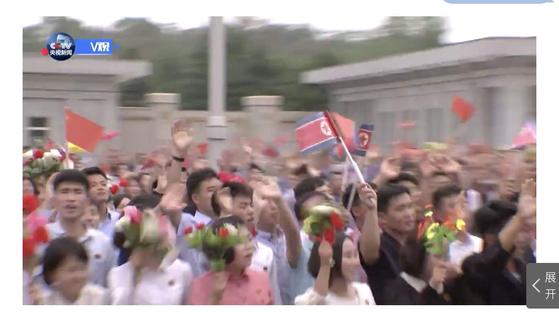 시진핑 중국 국가 주석이 20일 북한을 방문한 가운데 북한 주민들이 인공기와 중국국기, 꽃술을 흔들며 환영하고 있다. [사진 CCTV캡처]