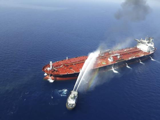 이란 해군 소속 선박이 지난 13일 오만해에서 공격을 받아 불이 난 유조선에 접근해 진화 작업을 벌이고 있다. [AP=연합뉴스]
