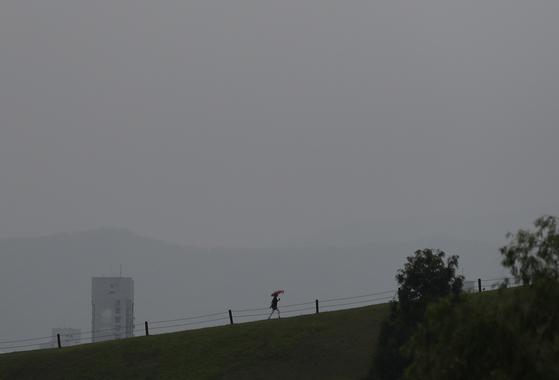 비가 내리는 18일 오후 서울 송파구 올림픽공원에 우산을 쓴 시민이 산책을 하고 있다. [연합뉴스]