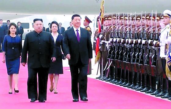 북한을 방문한 시진핑 중국 국가주석이 20일 평양 순안공항에 도착해 김정은 북한 국무위원장과 의장대를 사열하고 있다. 왼쪽부터 이설주 여사, 김 위원장, 펑리위안 여사, 시 주석. [뉴시]