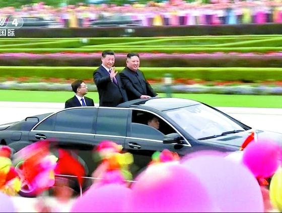 김정은 북한 국무위원장과 시진핑 중국 국가주석이 20일 평양 시내에서 함께 카퍼레이드를 하며 거리의 환영 인파를 향해 손을 흔들고 있다. [신화=연합뉴스]