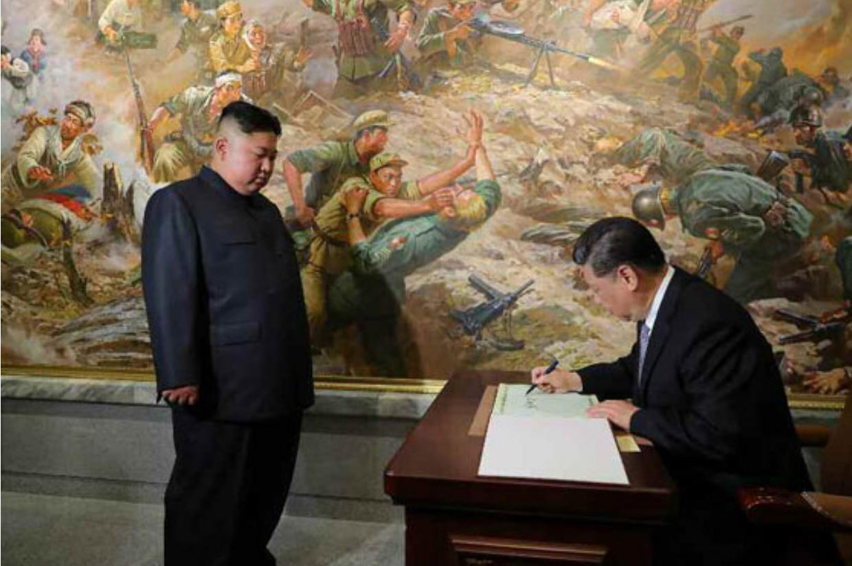 김정은 북한 국무위원장이 21일 우의탑에서 시진핑 중국 국가주석이 방명록 쓰는 모습을 지켜보고 있다. [뉴시스]
