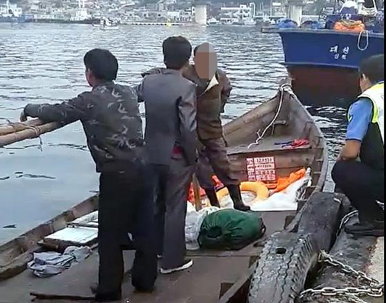 지난 15일 북한 선원 4명이 탄 어선이 연안에서 조업 중인 어민의 신고로 발견됐다는 정부 당국의 발표와 달리 삼척항 부두에 정박, 현장에 출동한 해양경찰에 조사 받는 영상이 공개됐다. 사진은 당시 삼척항 부두에 정박한 북한어선과 어민이 경찰에 조사받는 모습. [뉴스1]