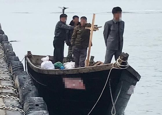지난 15일 강원 삼척항 부두에 정박한 북한 어선과 어민. [뉴스1]