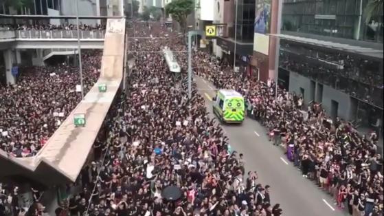 지난 16일 시위가 벌어지는 동안 실신한 시민을 후송하는 구급차가 지나가자 시민들이 길을 터주면서 '홍콩판 모세의 기적'이 벌어지고 있다. 시위가 민주주의 겨육을 받은 홍콩 시민들의 주도로 질서정연하게 이뤄지고 있음을 전 세계에 알린 사건이다. [홍콩=신경진 특파원]