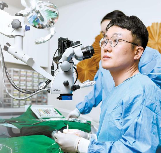 한그루치과 박진성 원장이 치아의 복잡한 신경 구조와 세균을 25배 확대해 볼 수 있는 정밀기기인 미세현미경을 이용해 죽어가는 치아를 살리는 난도 높은 신경치료를 하고 있다. 김동하 기자