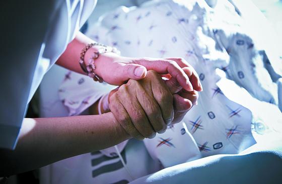서울성모병원의 호스피스 병동에서 호스피스팀 간호사가 말기 환자의 손을 맞잡고 있다. [중앙포토]