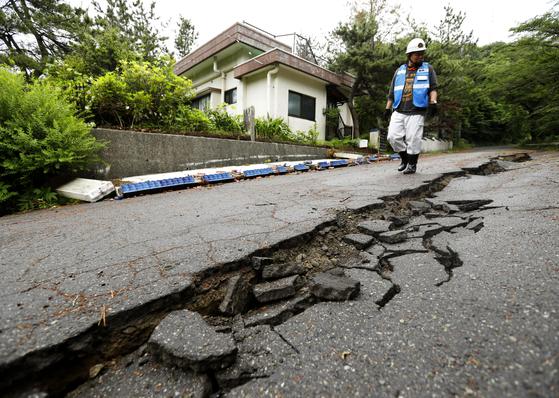지난 18일 일본 야마가타 현에서 발생한 지진 피해 상황을 이튿날 공무원이 살펴보고 있다. [AP]