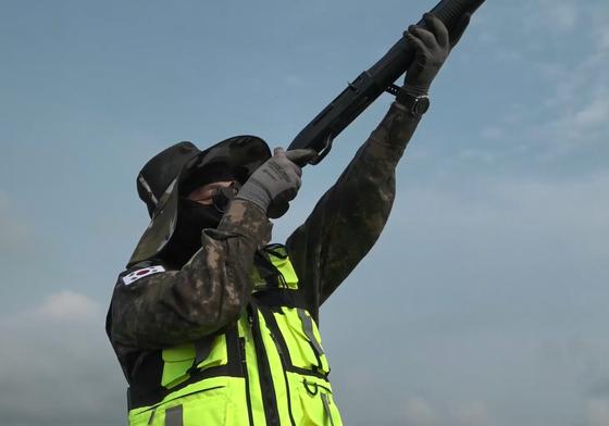 16일 경남 사천 공군 제3훈련비행단에서 조류 퇴치하는 임무는 가진 '배트맨'(BAT, Bird Alert Team)이 하늘을 향해 엽총을 들어 사격하고 있다. [영상캡처 = 강대석 기자]