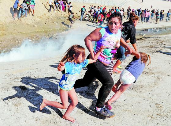미 캘리포니아주 샌디에이고와 접경을 이루는 멕시코 티후아나에서 미국 쪽으로 국경 진입을 시도하던 온두라스 출신 이주민 모녀가 국경수비대가 발사한 최루탄을 피해 뛰어가는 장면[로이터=연합뉴스]
