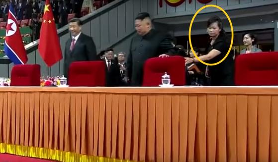 현송월(원 안) 당 선전선동부 부부장이 지난 20일 김정은 북한 국무위원장과 방북중인 시진핑 중국 국가주석의 대집단체조와 예술공연 관람시 주석단에서 김 위원장을 챙기고 있다. [조선중앙TV 캡처]