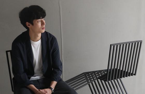 '일상의 자세, 의자, 그리고 사람' 전시에 참가하는 김충재 디자이너가 19일 서울 동대문 DDP 갤러리 문 전시관에서 자신이 디자인한 오래된 연인을 상징하는 의자에 앉아 포즈를 취하고 있다. 우상조 기자