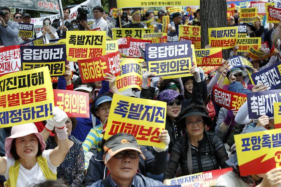 3일 오후 서울 여의도 국민은행 앞에서 열린 11·15지진 포항범시민대책위원회 '포항지진피해특별법 제정 촉구 집회'에서 포항 시민들이 구호를 외치고 있다. [뉴스1]