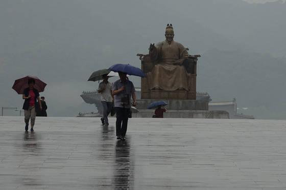 26일 제주와 남부지방에 장마가 시작되겠다. 평년에 비해 열흘가량 늦은 지각 장마다. 장마전선이 더 북상할 경우 중부지방에도 26~27일 장맛비가 내릴 가능성이 있다고 기상청은 밝혔다. 사진은 지난해 7월 11일 아침 장맛비가 내리는 서울 광화문 광장을 직장인들이 우산을 쓰고 지나는 모습이다. [연합뉴스]