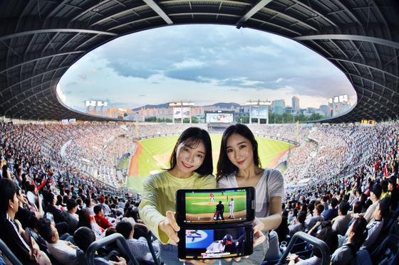 5G 시대가 열리면서 프로야구 중계에 큰 변화가 생겼다. 관중들은 U+ 프로야구 앱을 통해 주요 장면을 돌려보고 경기장 구석구석을 확대해 볼 수 있게 됐다. 모델들이 잠실야구장을 배경으로 U+프로야구를 소개하고 있다. [사진 LG유플러스]