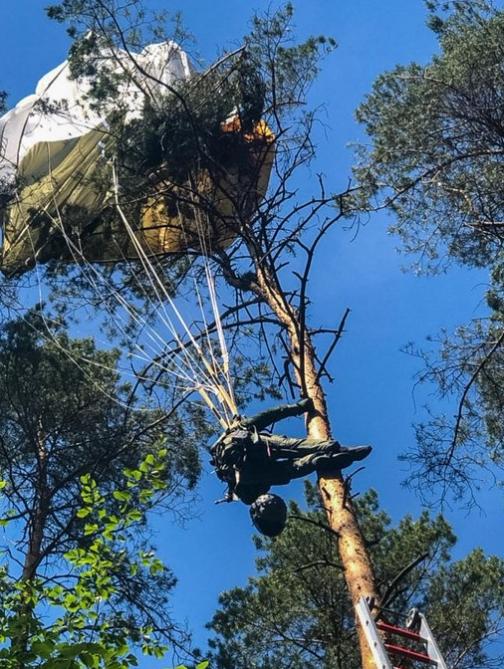 이날 추락한 전투기에서 낙하산을 펴고 비상탈출한 조종사 중 생존한 한 명이 나무 위에 낙하산이 걸린 채 구조를 기다리고 있다. [사진 트위터]