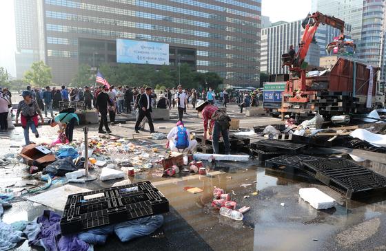 서울시는 25일 새벽 광화문광장의 대한애국당 천막을 기습 철거했다. 천막 잔해가 세종대로에 널려 있다. 최정동 기자 20190625