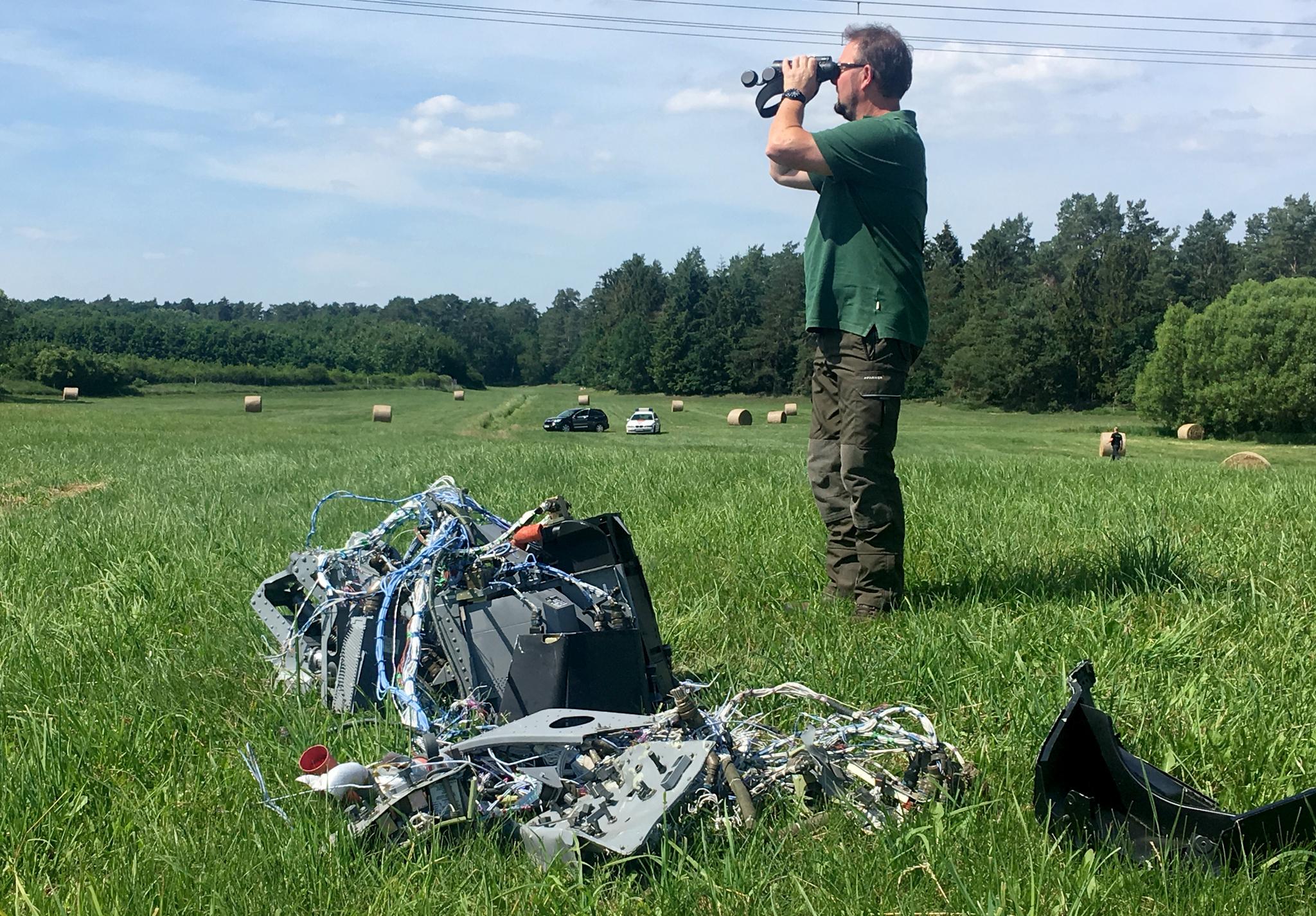 24일(현지시간) 전투기 추락 인근 지역에 떨어진 전투기 잔해 옆에서 한 시민이 쌍안경으로 추락지점을 살펴보고 있다. [EPA=연합뉴스]