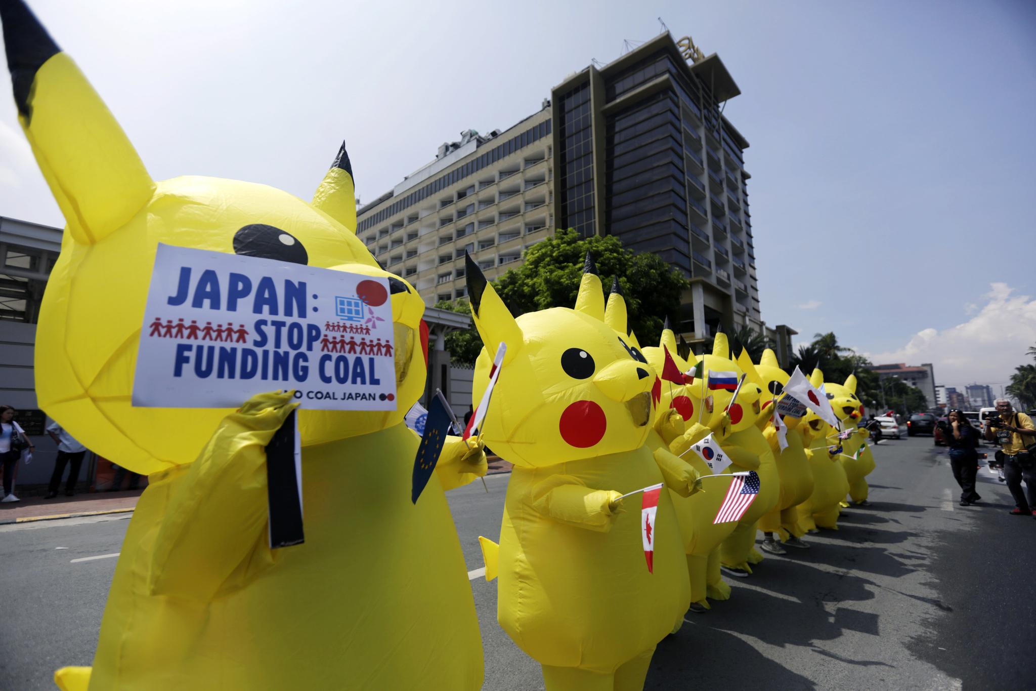 피카츄 복장을 한 환경운동가들이 25일(현지시간) 필리핀 수도 마닐라 일본 대사관 앞에서 G20 참가국 국기를 들고 시위하고 있다. [EPA=연합뉴스]