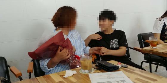 '딸이 죽었다'는 목사 농간으로 헤어진 A씨(39)와 딸 B양(15)이 지난 22일 전북 익산의 한 장애인복지시설에서 15년 만에 만나 손 잡고 얘기를 나누고 있다. [사진 익산경찰서]