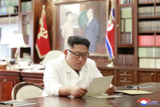 김정은 북한 국무위원장이 도널드 트럼프 미 대통령의 친서를 읽고 있다. 북한은 지난 23일 이 사진을 공개했다. [사진 조선중앙통신]