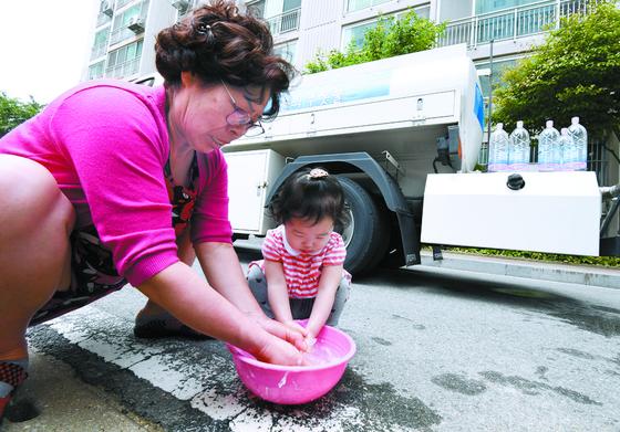 지난 21일 오후 붉은 수돗물이 나온 서울 영등포구 문래동의 아파트에서 한 어린이가 급수차로부터 공급받은 물로 손을 씻고 있다. [뉴스1]