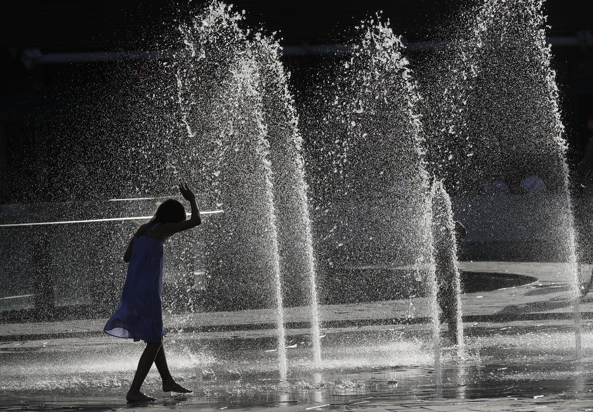24일(현지시간) 이탈리아 밀라노에서 한 소녀가 분수에서 물을 뿌리며 더위를 식히고 있다.[AP=연합뉴스]