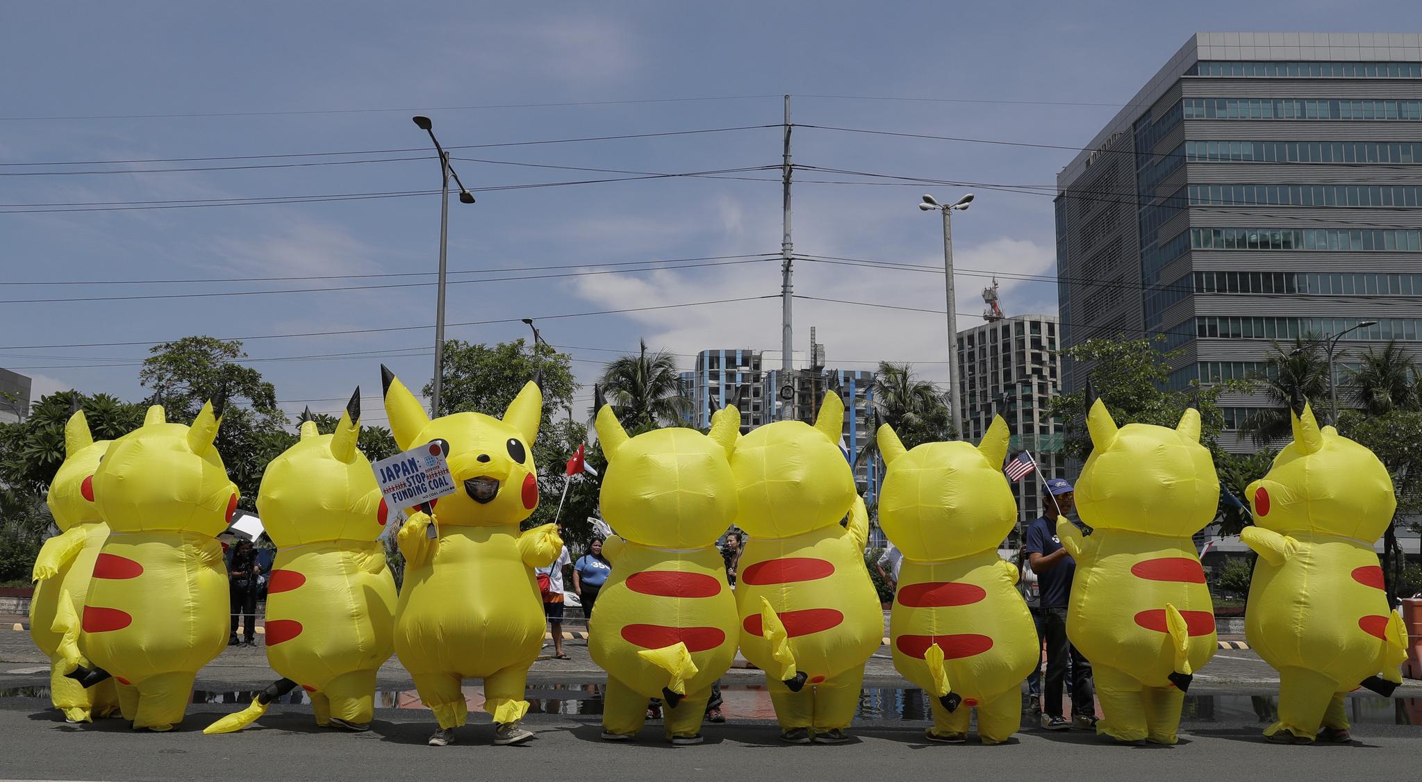 피카츄 복장을 한 환경운동가들이 25일(현지시간) 필리핀 수도 마닐라 일본 대사관 앞에서 G20 참가국 국기를 들고 시위하고 있다. [AP=연합뉴스]