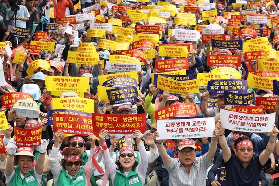 서울개인택시운송조합 조합원들이 지난 19일 오후 서울 종로구 KT 광화문빌딩 앞에서 열린 '타다 서비스 중단 촉구 집회'에서 구호를 외치고 있다. [뉴스1]