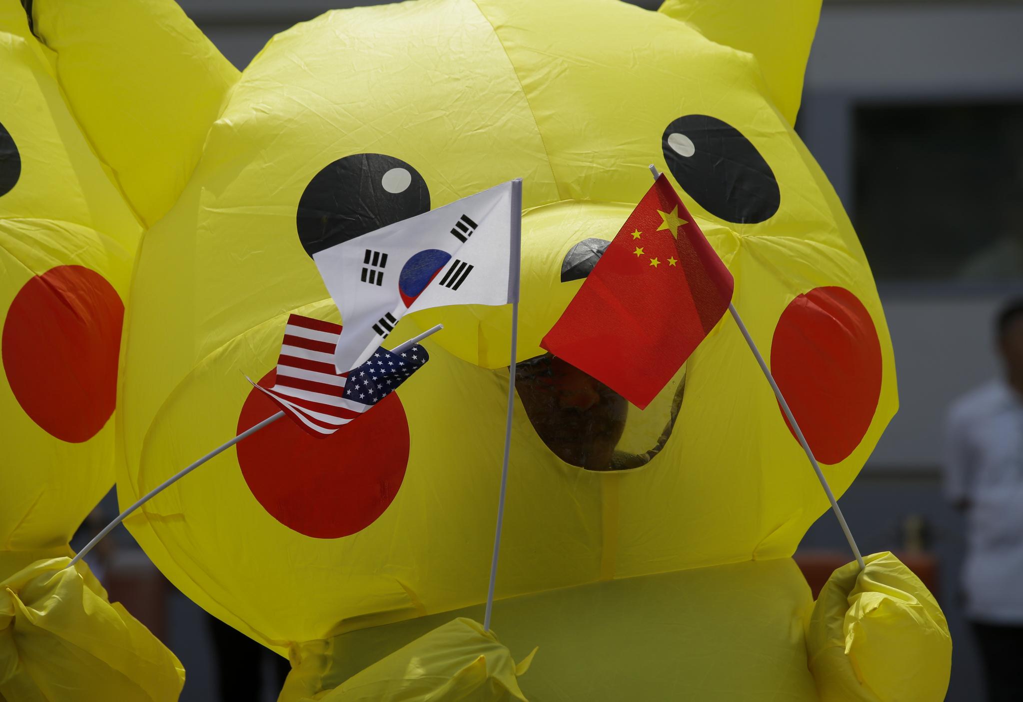 피카츄 복장을 한 환경운동가들이 25일(현지시간) 필리핀 수도 마닐라 일본 대사관 앞에서 태극기, 오성홍기 성조기 등 G20 참가국 국기를 들고 시위하고 있다. 시위대는 G20 정상회담을 준비하는 일본이 석탄화력발전 사업에 대한 자금지원을 중단할 것을 촉구하고 있다. [AP=연합뉴스]