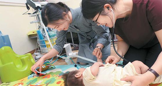 서울대병원 김민선 교수(오른쪽)와 원미현 간호사가 가정집에서 인공호흡기를 차고 있는 중증소아환자 다온이를 진료하고 있다. [최정동 기자]