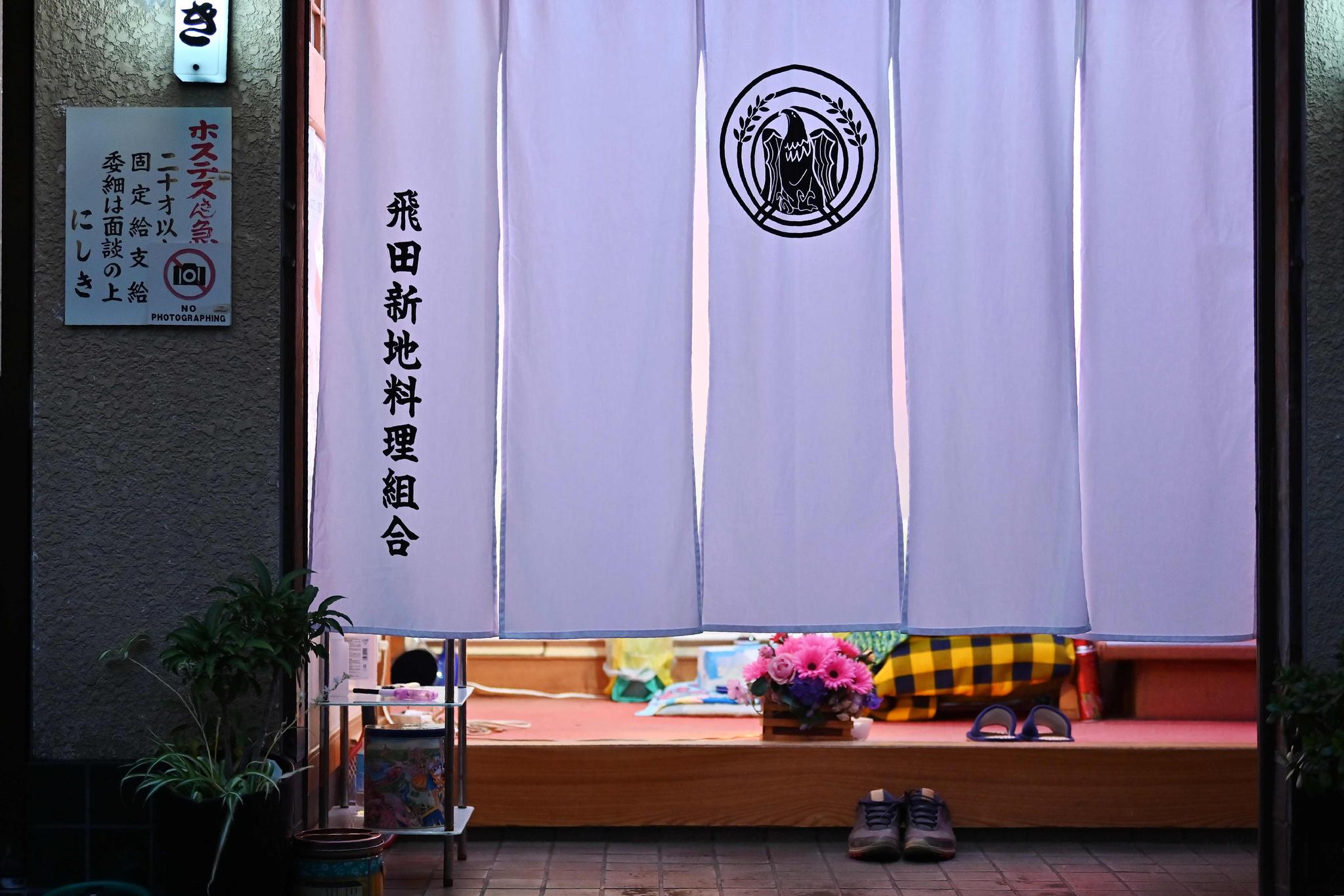 일본 오사카 시의 홍등가인 '토비타신치'의 한 점포에 26일 흰 커튼이 내려져 있다. 토비타신치 협동조합은 성공적인 G20 개최를 위해 쇼 윈도를 가린 채 영업할 예정이며, 회담일인 28일과 29일에는 임시 휴업할 것이라고 밝혔다. [AFP=연합뉴스]