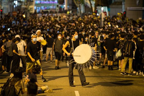 수백명의 시위대가 26일 밤 경찰본부 앞에서 항의시위를 하고 있다. 이들은 도심에서 열린 집회를 마치고 경찰본부로 몰려와 지난 12일 시위현장에서 발생한 경찰의 강경진압에 항의했다.[EPA=연합뉴스]