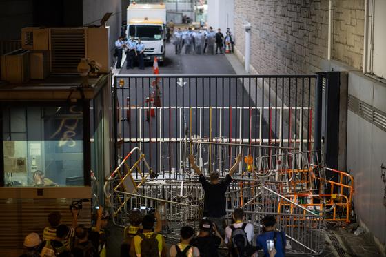 27일 새벽 시위대가 경찰본부 정문을 바리케이드로 봉쇄한 후 경찰과 대치하고 있다.[AFP=연합뉴스]