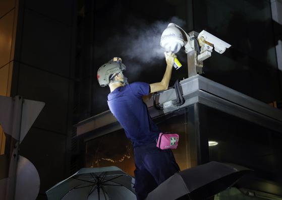 시위대가 26일 밤 경찰본부 앞 CCTV 카메라에 스프레이를 뿌리고 있다.[AP=연합뉴스]