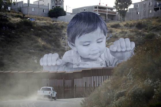 미국-멕시코 국경에 설치된 멕시코 어린이의 얼굴이 그려진 벽화. 트럼프 미국 대통령이 청소년 대상 이민 규제를 강화한 데 따른 항의 표시다.  [AP=연합뉴스]