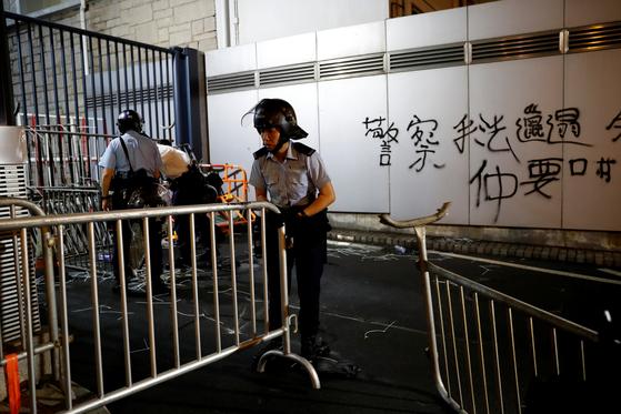경찰들이 27일 새벽 시위대가 만든 정문 앞 바리케이드를 치우고 있다.[로이터=연합뉴스]