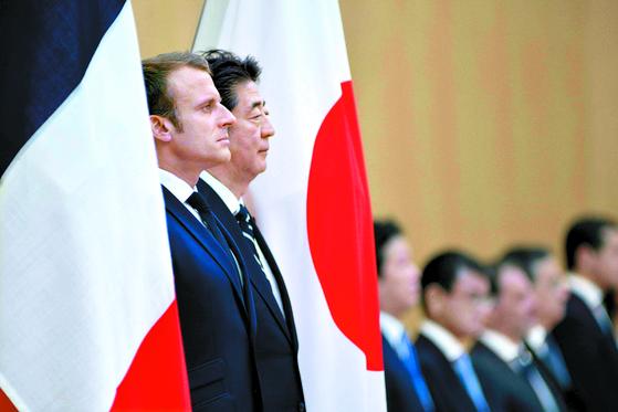 일본을 방문한 에마뉘엘 마크롱 프랑스 대통령(왼쪽)과 아베 신조 총리가 26일 도쿄 총리공관에서 열린 일본-프랑스 정상회담에 앞서 열린 공식 환영식에서 의장대를 사열하고 있다. 마크롱 대통령은 오는 28~29일 오사카에서 열리는 G20 정상회의에 참석할 예정이다. [AP=연합뉴스]